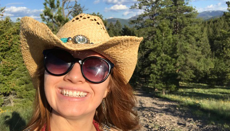 Liv Schneider in Montana countryside with cowgirl hat