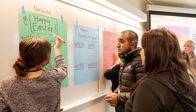 teacher and students review holiday words on a board