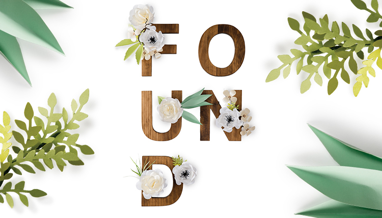 Wooden letters spelling 'Found' framed by paper flowers and leaves