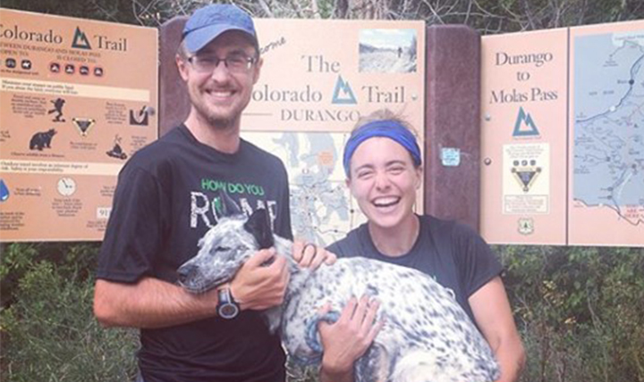 Williams and Devereaux smile with their dog Aska at the trailhead.