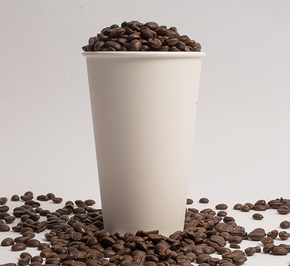 Coffee beans fill a coffee cup.