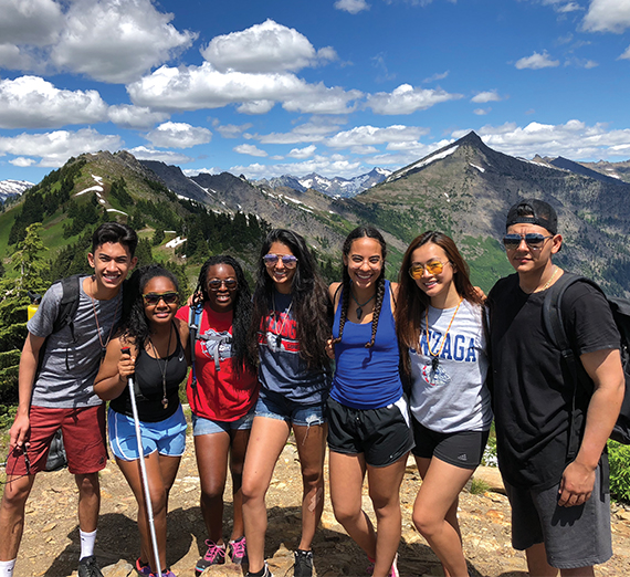 The Act Six scholars pose on top of a hike in the mountains.