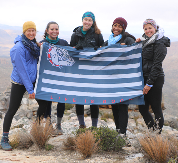 The five Gonzaga student studying abroad in Stellenbosch pose with a Gonzaga flag.