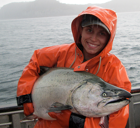 the author in a fishermans jacket holding a large fish