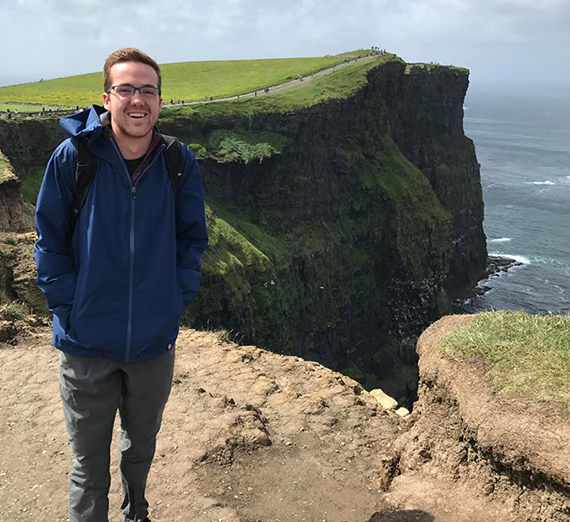 Konner Sauve stands on a cliff overlooking the sea in Ireland.