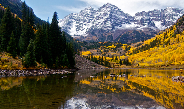 The Maroon Bells peaks are seen surrounded by fall colors.