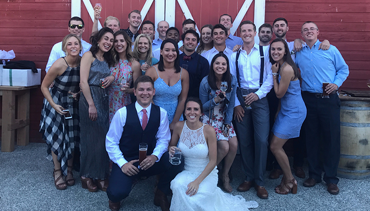 couple surrounded by friends in front of barn