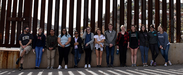 Students stand for a picture in front of the border wall near Nogales