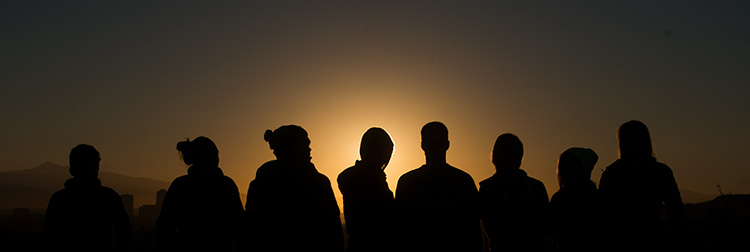 A group of students are silhouetted against the sunset