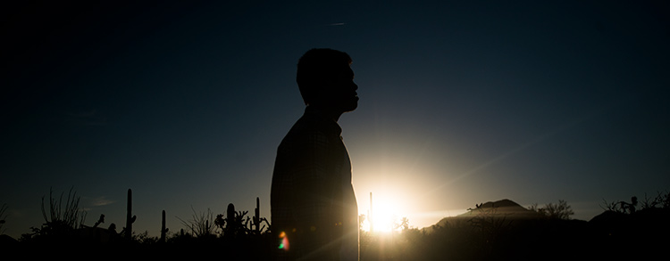 A student stands silhouetted against the sun