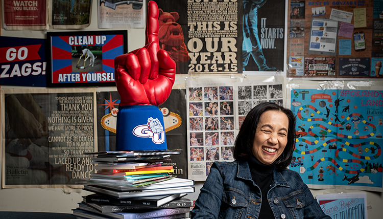 shiosaki at her desk with piles of memorabilia around her