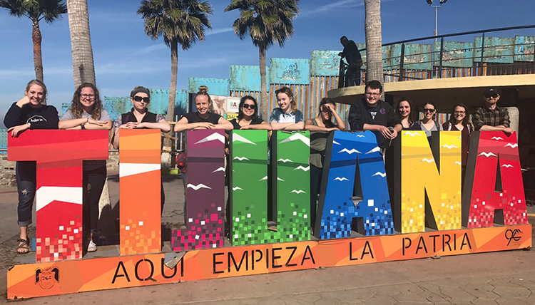 Gonzaga students pose at colorful Tijuana sign on the beach in Mexico