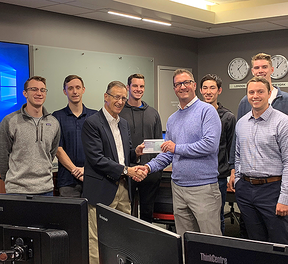 Students in Professor Bud Barnes' current investment class receive the check on behalf of the 2017-18 class, which won the award. Michael Jackson, branch manager for D.A. Davidson's Spokane office, presents the check to Barnes. GU photo