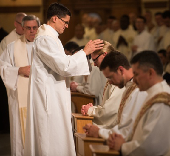 A priest offers blessings to newly ordained Jesuits.