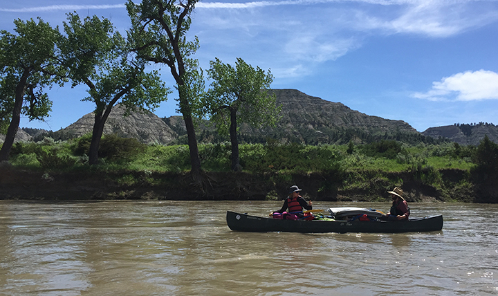 Two people paddle a canoe down the Missouri River