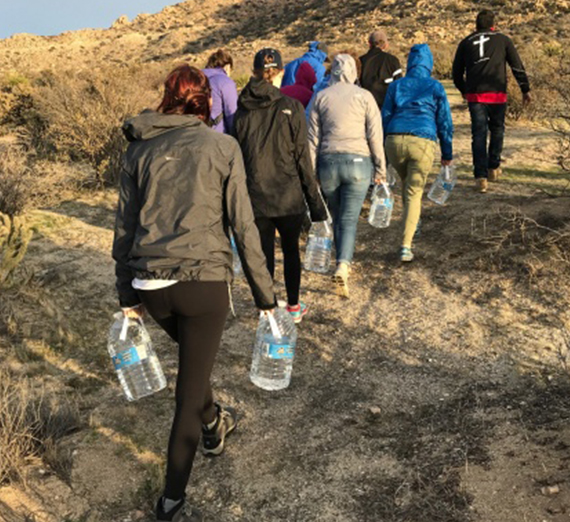 Students carry water jugs through the desert near the Mexico-US border.