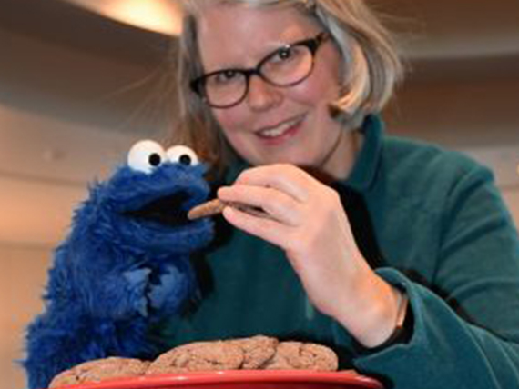 Molly McFadden holds a homemade cookie and her Cookie Monster puppet.