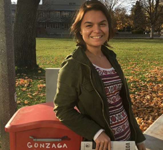 Student Sidnee Grubb stands next to a mailbox holding a ballot.