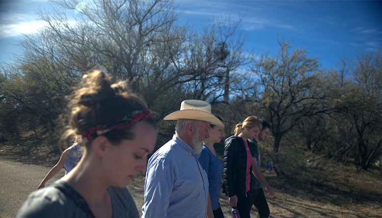 Fr. Pete Neeley walks with Gonzaga students into the bright sun of the Sonoran Desert