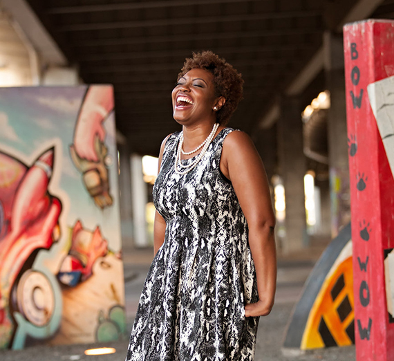 African-American woman standing around colorful pieces of art and laughing