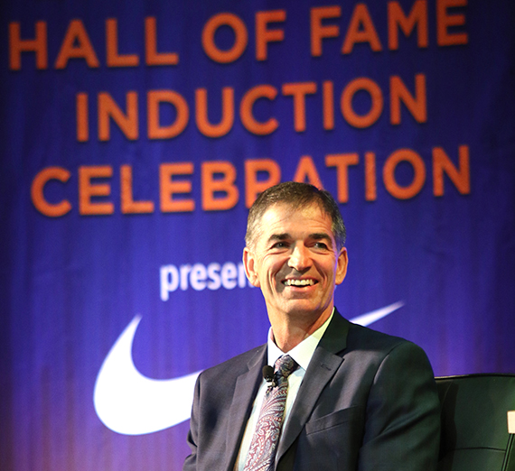 John Stockton smiling in front of a banner that denotes his induction into the Basketball Hall of Fame