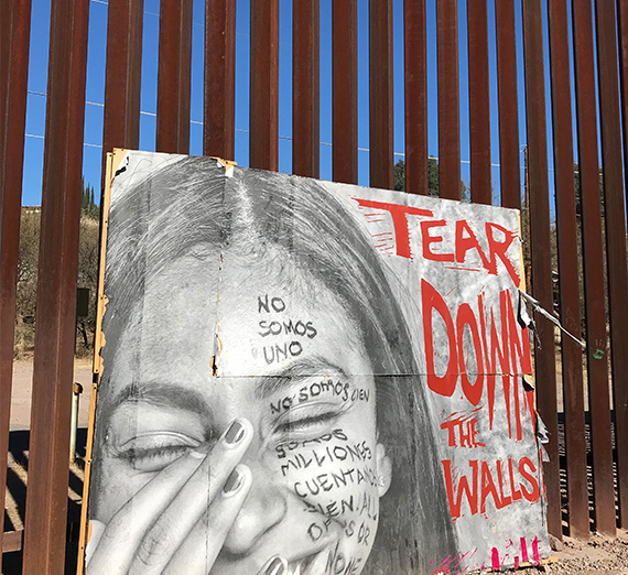 "a sign at the wall separating Mexico from the U.S. reads ""tear down the walls"""