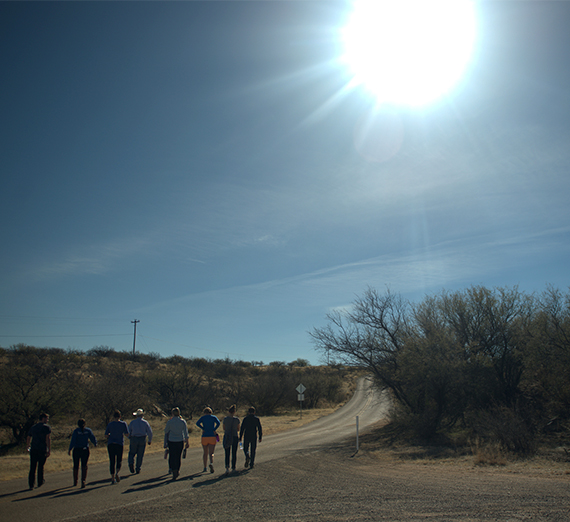 sun shining over walkers in Sonoran Desert