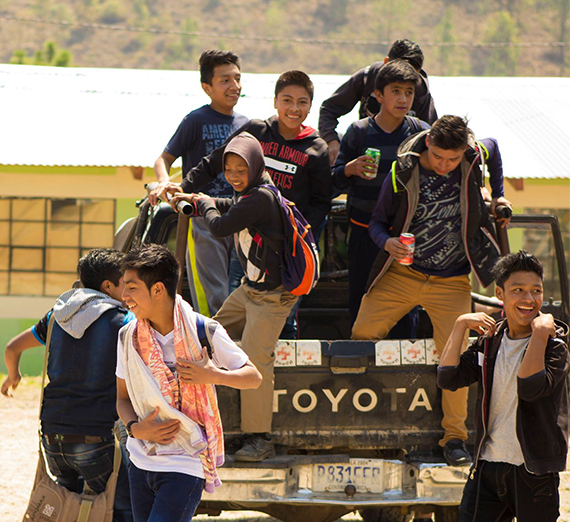 Smiling Guatemalan children climb out of the back of a Toyota pickup