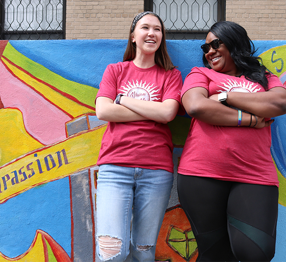 Two girls smile and pose in front of a colorful mural outside a nonprofit in New York City.