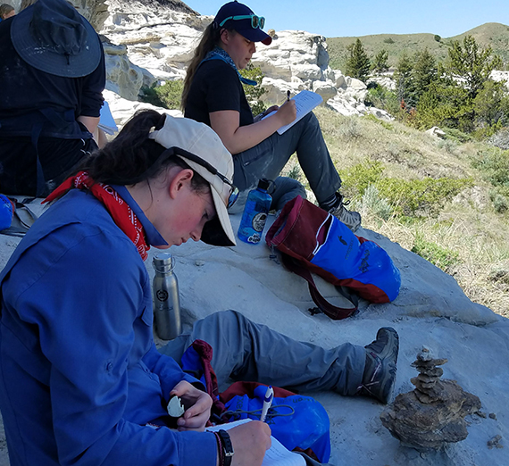 Students sit in the shade of a cliff while journaling outdoors.