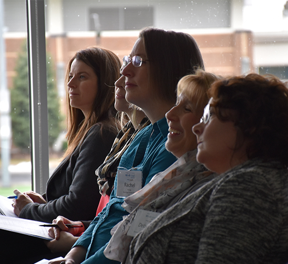 5 women sit at conference smiling