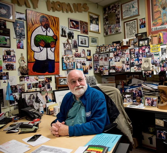 Father Greg Boyle sits in his picture and painting filled office.