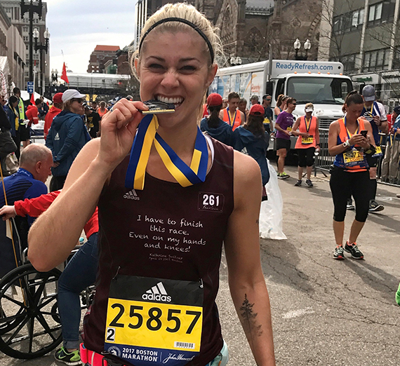 Lauren Zeutenhorst bites medal after finishing Boston Marathon