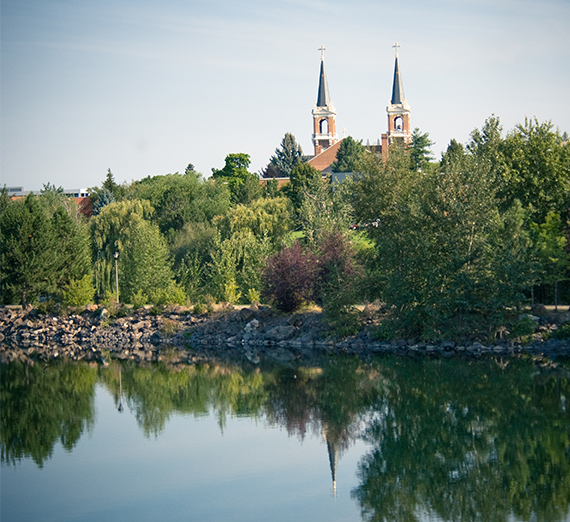 The spires of St. Aloysius Church are reflected in the waters of Lake Arthur