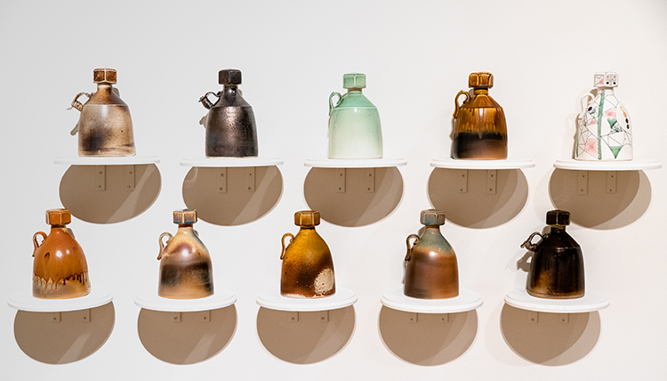 Two rows of five growlers with screw top lids, cast porcelain by Mat Rude from the GU Art Department Faculty Exhibition