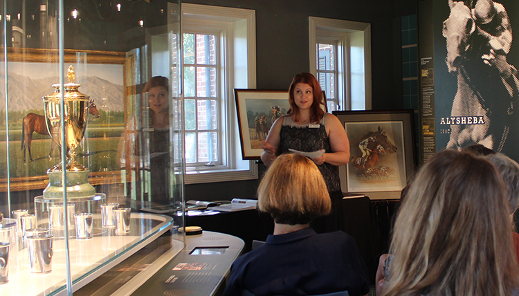 Jenni presents to a gathering at a museum exhibit