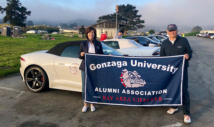 Two members of the Gonzaga Grand Prix hold a Gonzaga alumni flag in front of their car.