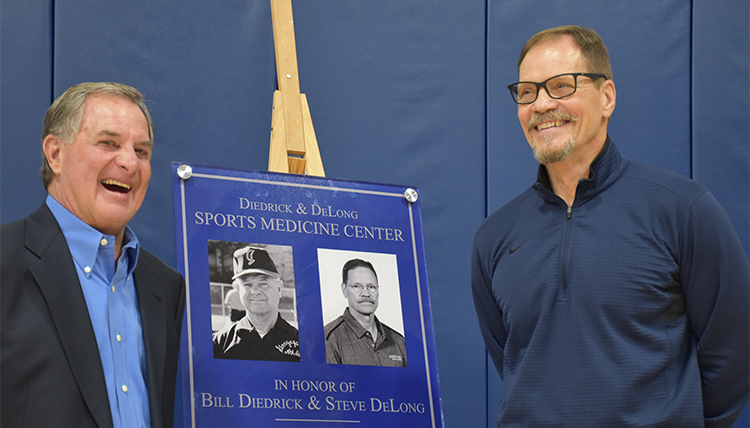 Bill Diedrick and Steve DeLong stand with old photos of them during a dedication ceremony