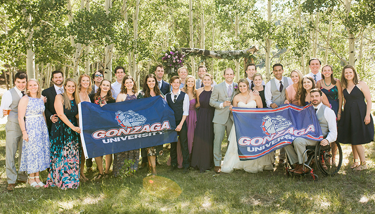 A group of wedding guests standing outside, holding two Gonzaga University flags.