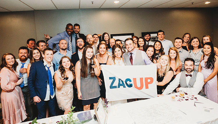 A group of wedding guests indoors, smiling and holding a 'Zag Up' flag.
