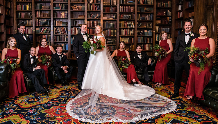 A bride and groom standing in a library, surrounded by books and in the company of bridesmaids - in red dresses - and groomsmen - in black suits.