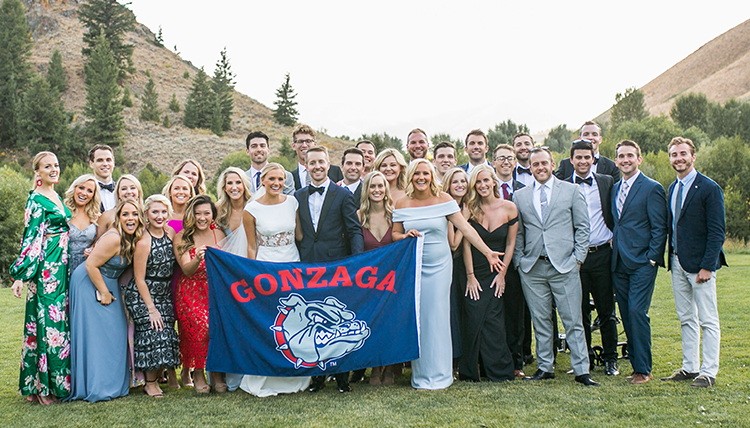 large wedding party outdoors with GU flag