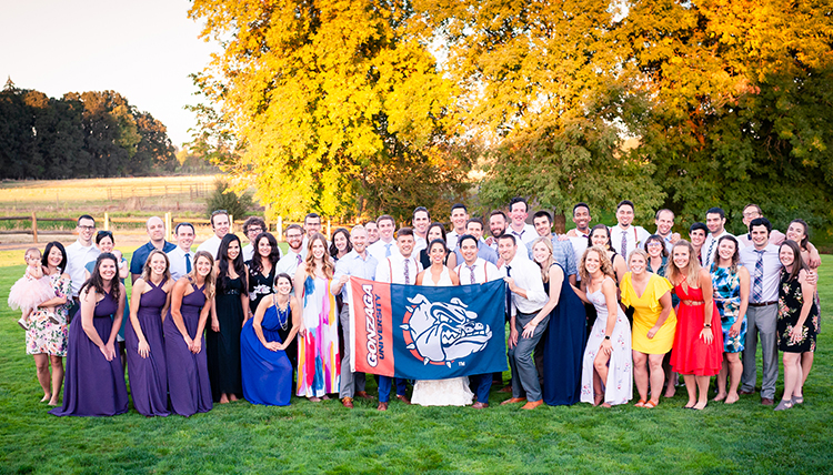 large wedding party outdoors with people holding bulldog flag