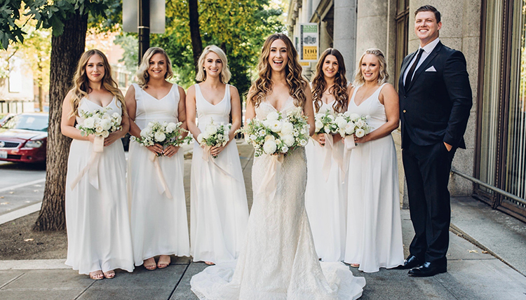 bride surrounded by bridesmaids in white and groom