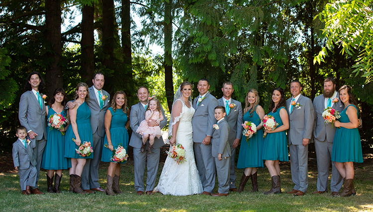 large wedding party with women in teal dresses and men in gray suits