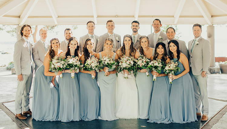 large wedding party with women in blue and men in gray