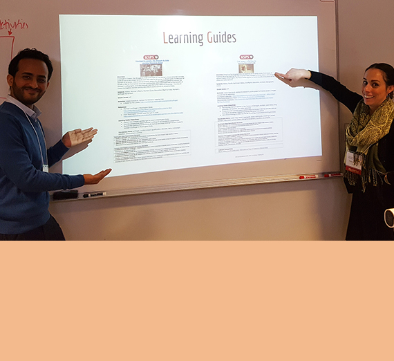 Two graduate teaching students show off their work on a slide.
