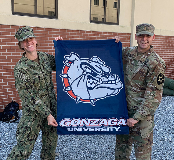 Two Airborne grads hold a Gonzaga flag