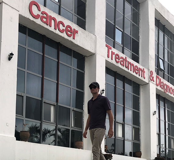 young alum walks in front of cancer center in Africa