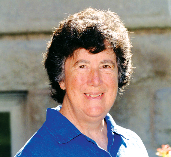 Woman (Sister Mary Garvin) with short, dark hair and a blue, collared shirt smiling.